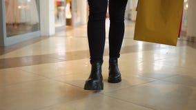 Посмотрите ноги женщины идя с хозяйственными сумками вокруг мола сток-видео