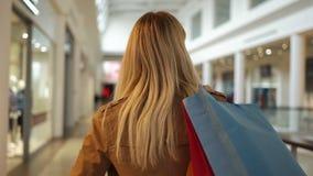Посмотрите от заднего на милой женщине идя с хозяйственной сумкой и завихряясь вокруг в моле акции видеоматериалы