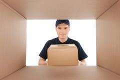 Посмотрите от картонной коробки. Жизнерадостное молодое удерживание работника доставляющего покупки на дом Стоковые Изображения RF
