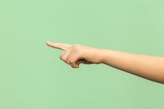 Посмотрите это! Вручите указывать пальца изолированный на зеленой предпосылке стоковая фотография rf