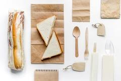 Поставка еды с бумажными сумками и модель-макетом взгляд сверху предпосылки сандвича белым Стоковые Фотографии RF