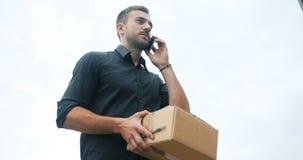 Поставка курьера с пакетом используя мобильный телефон, говоря ждать клиента сток-видео