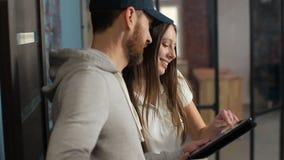 Поставка, почта, люди и концепция доставки - счастливый человек поставляя коробки пакета к дому клиента Давать доску сзажимом для видеоматериал
