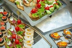 Поставляя еду закуски установленного обслуживания таблицы различные на таблице на банкете Комплект холодных закусок, канапе, напи стоковая фотография