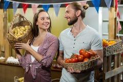 Поставщики женщины и человека держа корзину томатов и картошек Стоковое фото RF