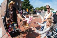 Поставщик воздушного шара животный делает кота для девушки на фестивале Стоковые Фото