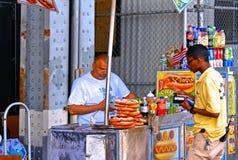 Поставщик еды улицы хот-дога, кренделя и напитков с костюмом около Бруклинского моста внутри в Манхэттене, Нью-Йорке стоковые фотографии rf