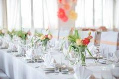 Поставьте сервировку на обсуждение с блюдами, стеклами и цветками в зале Стоковое Изображение