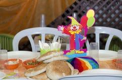 Поставьте украшение на обсуждение на празднике Purim - клоуна, хлеб pitta и 2 белых пластичных стуль Стоковые Фото