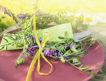 Поставьте украшение на обсуждение с цветками вики и зеленой тканью на красной плите Стоковые Изображения