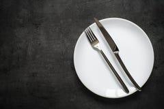 Поставьте установку на обсуждение Нож вилки и белая плита на темной таблице шифера Стоковые Фото