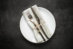 Поставьте установку на обсуждение Нож вилки и белая плита на темной таблице шифера Стоковая Фотография RF