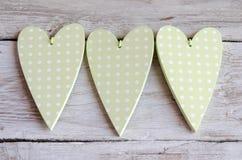 Поставленные точки бледные ые-зелен сердца на деревянной предпосылке Стоковое Изображение