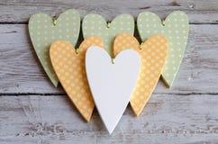 Поставленные точки бледные ые-зелен сердца на деревянной предпосылке Стоковое Изображение RF