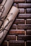 Постаретая бумага свертывает с строкой на плетеной циновке места Стоковые Фото