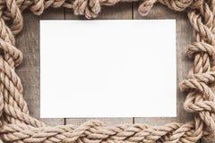Постаретая бумага с рамкой веревочки на старой деревянной предпосылке Стоковые Фото