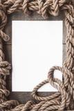 Постаретая бумага с рамкой веревочки на старой деревянной предпосылке Стоковая Фотография