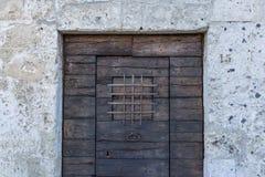 Постаретая винтажная деревянная дверь с каменной пещерой здания в Matera, sou Стоковое Изображение RF