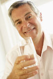 постаретая вода середины человека выпивая стекла Стоковое Фото