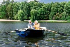 Постаретая жена и супруг держа затворы имея славное отключение реки в шлюпке стоковые фотографии rf
