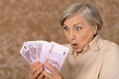 Постаретая женщина держа деньги Стоковое Изображение