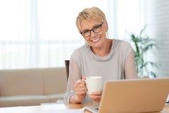 Постаретая женщина работая от дома Стоковая Фотография