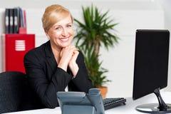 Постаретая коммерсантка сидя с руками на подбородке Стоковое Изображение