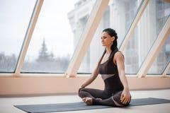 Постаретая серединой концепция йоги привлекательной женщины yogi практикуя, сидя в половинной тренировке лотоса, представление Si Стоковые Изображения