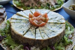 Постаретое колесо голубого сыра с клином, отрезком в малых треугольниках на ресторане шведского стола стоковая фотография