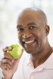 постаретое яблоко есть середину зеленого человека Стоковые Фотографии RF