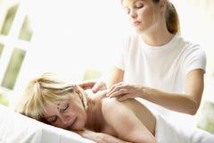 постарето наслаждающся женщиной середины массажа стоковая фотография