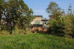 Постаретые дома сельской местности в деревьях и заводы солнечного afte зимы Стоковые Фото