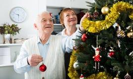 Постаретые пары украшая рождественскую елку Стоковые Изображения