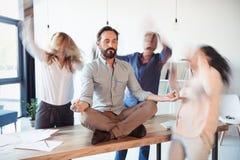 Постаретый бизнесмен сидя на таблице и размышляя в положении лотоса пока коллеги бежать вокруг Стоковая Фотография RF