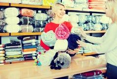 Постаретый женский продавец демонстрируя покрывала к молодому покупателю стоковое изображение rf