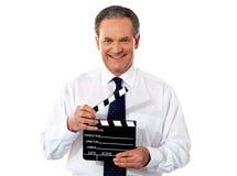 постаретый мужчина удерживания clapperboard корпоративный стоковые изображения rf