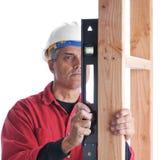 постаретый плотник проверяя ровные средние стержни Стоковые Изображения