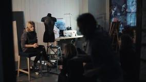 Постаретый серединой женский учитель дизайна моды сидя на стуле, говоря к студентам сток-видео