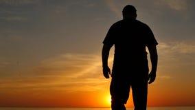 Постаретый человек выражая утеху с рукой вверх на силуэте замедленного движения захода солнца сток-видео