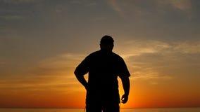 Постаретый человек выражая утеху с рукой вверх на силуэте замедленного движения захода солнца видеоматериал
