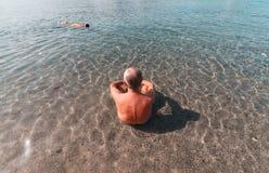 Постаретый человек принимая остатки на море в Италии - Сардинии стоковые фотографии rf