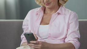 Постаретый экран мобильного телефона скроллинга женщины, усмехаясь на полученных фото, устройство акции видеоматериалы