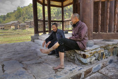 2 постарели китайские люди отдыхая в тени под настелинным крышу мостом Стоковое Изображение RF
