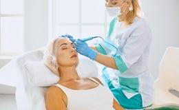 Постоянный состав для бровей Красивая женщина с толстыми челами в салоне красоты Beautician делая бровь татуируя для стоковые изображения rf