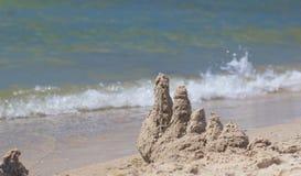 Построенный замок песка дома с башнями на южном береге моря сини песчаного пляжа Стоковая Фотография RF