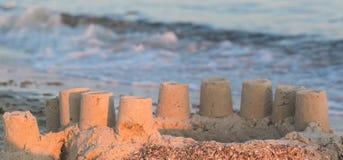 Построенный замок песка дома с башнями на южном береге моря сини песчаного пляжа Стоковое Изображение