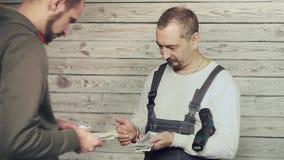 Построители рассматривают заработанные деньги акции видеоматериалы