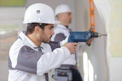 Построители сверля стену стоковое изображение
