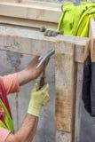 Построитель вручает бить ноготь молотком в планку 4 стоковые фотографии rf