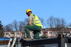 Построитель в прозодеждах на строительной площадке Ремонты на высоте конструкция зданий новая Профессия построителя Hea Стоковое фото RF